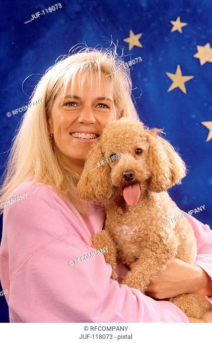 woman with poodle in front of christmas decoration