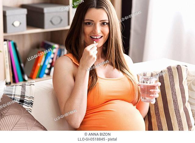 Pregnant woman taking vitamin pill. Debica, Poland