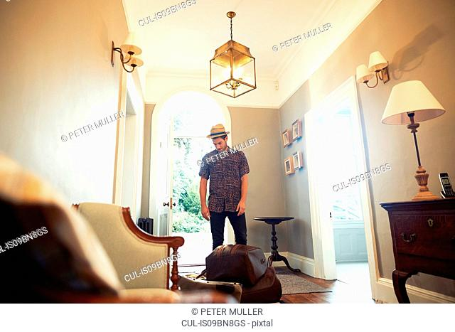 Young man in trilby looking down at luggage in hotel lobby