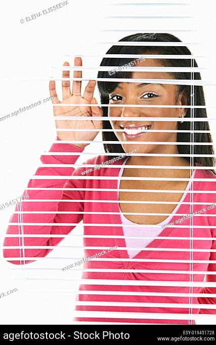 Smiling woman looking through blinds