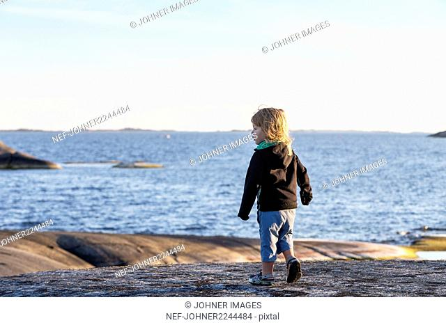 Boy playing by sea