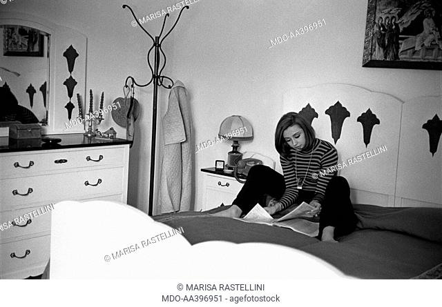 Raffaella Carrà reading on a bed. Italian TV presenter and showgirl Raffaella Carrà (Raffaella Roberta Pelloni) sitting on the bed and reading