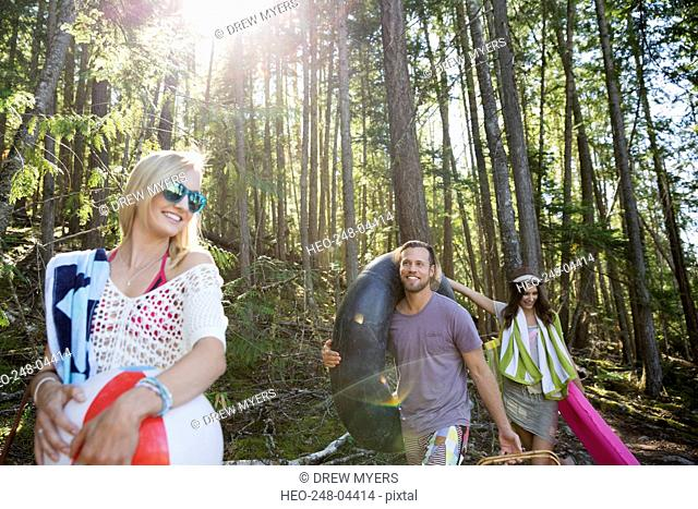 Young friends carrying pool rafts under trees