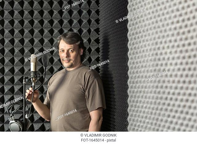 Portrait of mature male musician standing by microphone in recording studio