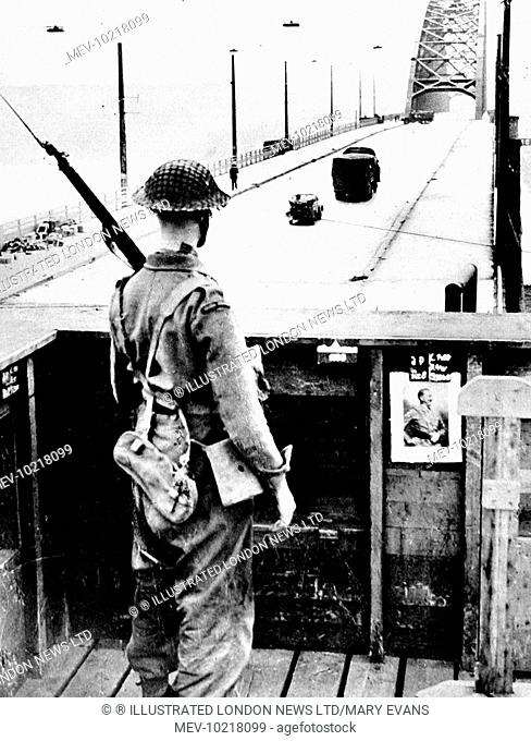 Photograph showing aan Irish Guardsman keeping watch on the Bridge at Nijmegen, September 1944. On 17th September 1944 Operation 'Market Garden' was put into...