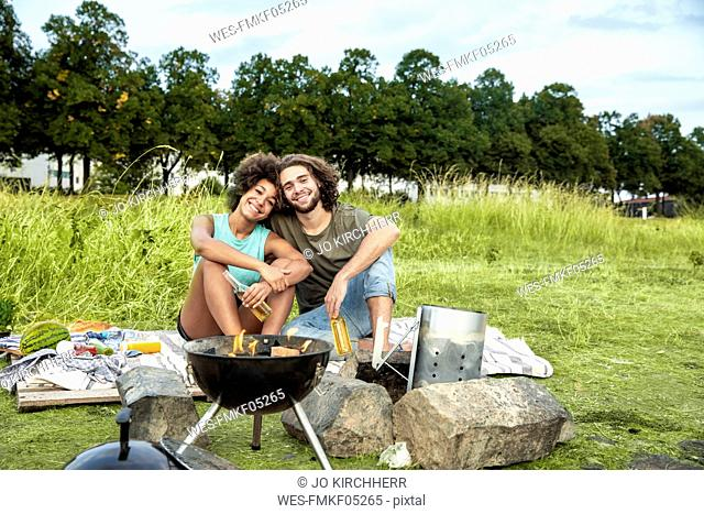 Happy couple having a barbecue in the nature