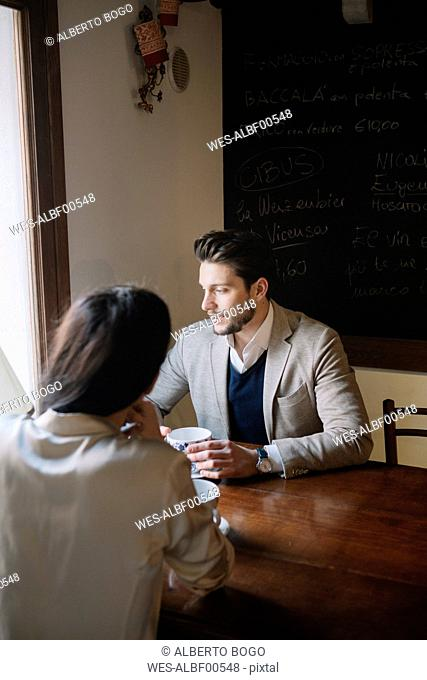 Elegant couple talking in a cafe