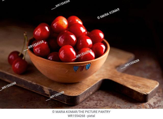 Fresh ripe cherries in a bowl on dark background