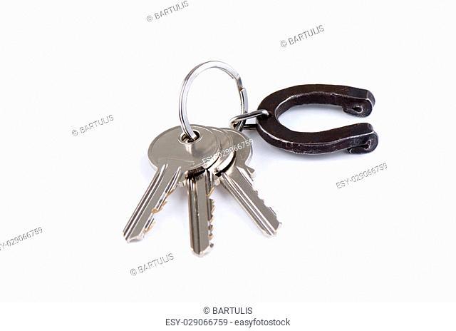 House keys with horseshoe on keyring isolated over white background