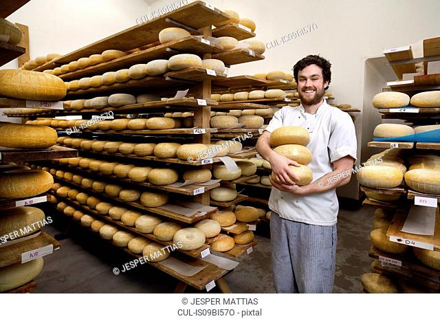 Portrait of cheese maker carrying hard cheeses for inspection, in ageing room where hard cheeses are stored