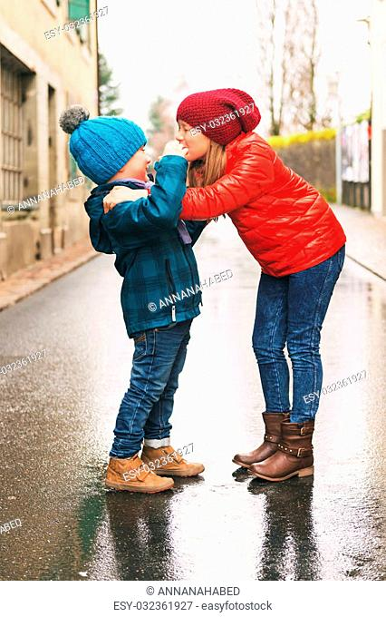 Big sister giving a hug to her small brother, kids wearing bright warm jackets