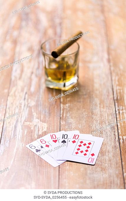 glass of whisky and playing cards on table