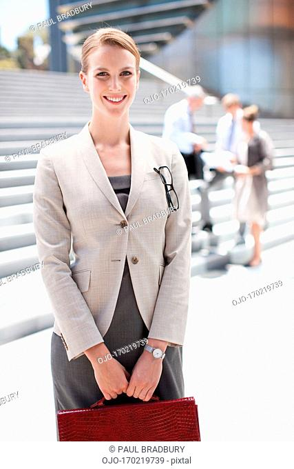 Businesswoman holding briefcase standing outdoors