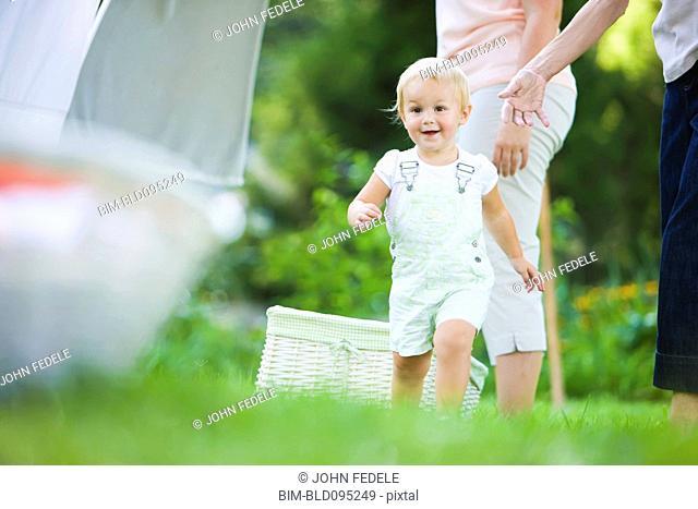 Caucasian baby running in grass