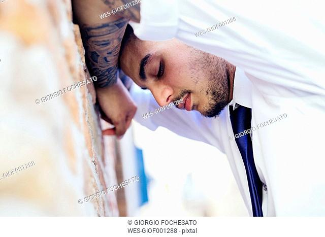 Young businessman with eyes closed leaning against brick wall, close-up