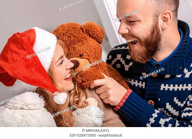 Beautiful couple in Santa hat and Christmas gifts. Merry Christmas background