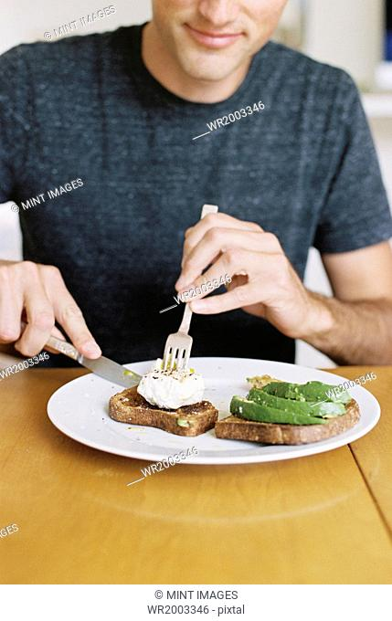 Man sitting in front of a plate of food at a table, eating