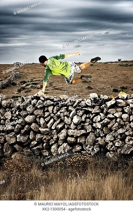 Young man jumping over dry stone wall. Minorca, Balearic Islansd, Spain