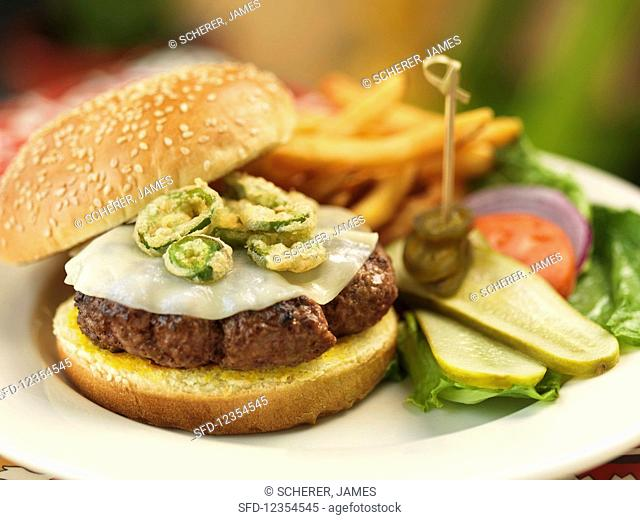 A cheeseburger with jalapenos, salad, and fries