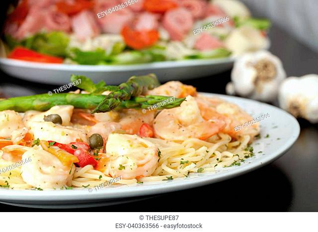 A delicious shrimp scampi pasta dish with antipasto salad in the background