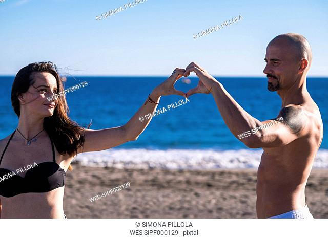 Spain, Tenerife, portrait of happy couple on the beach building a heart with her hands