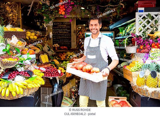 Fruiterer carrying tray of fruits in shop, Palma de Mallorca, Spain
