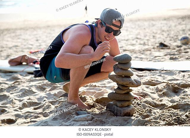 Young man crouching next to a stacked stones on beach