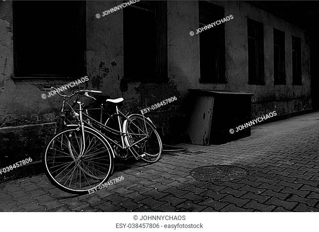 Vintage bikes over old wall. Black and white