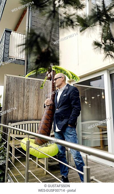 Senior businessman standing in his garden, holding a rubber palm, dreaming of vacations