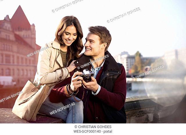 Germany, Berlin, young couple looking at camera at bank of River Spree