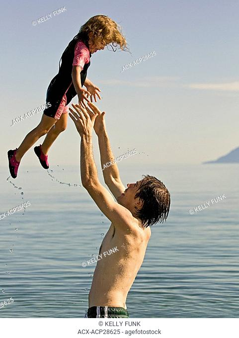A father and daughter share a moment on a beautiful summer day in the Pacific Ocean, near Powell River, on the Sunshine coast of the Vancouver coast and...