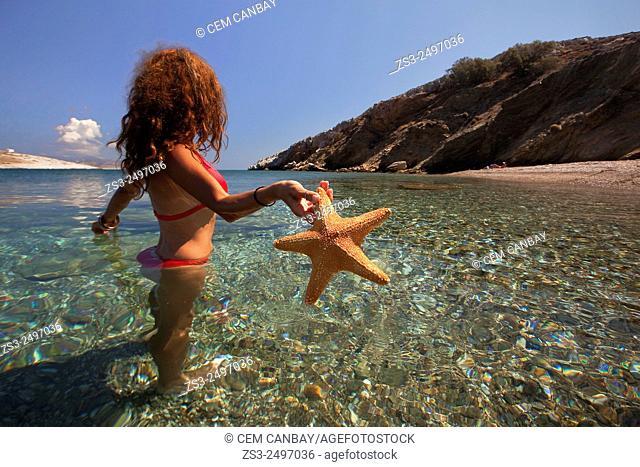 Woman in the sea with a starfish in her hand at Agios Georgios beach, Folegandros, Cyclades Islands, Greek Islands; Greece, Europe