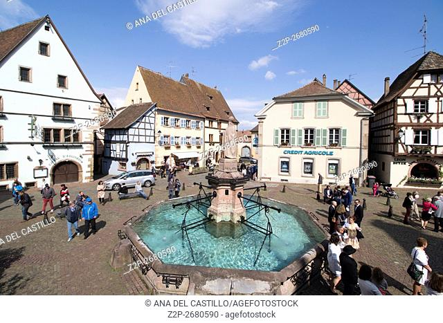 Eguisheim village, traditional colorful houses in Alsace, France. The fountain at the main square