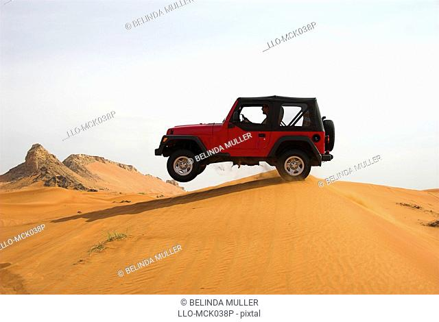 Red 4x4 Jumping over Dunes in the Desert  Hatta Desert, Dubai, United Arab Emirates
