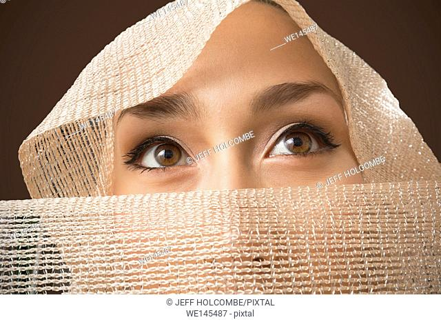 Beautiful young woman head shot portrait with tan scarf draped over head and face, only eyes showing, looking up