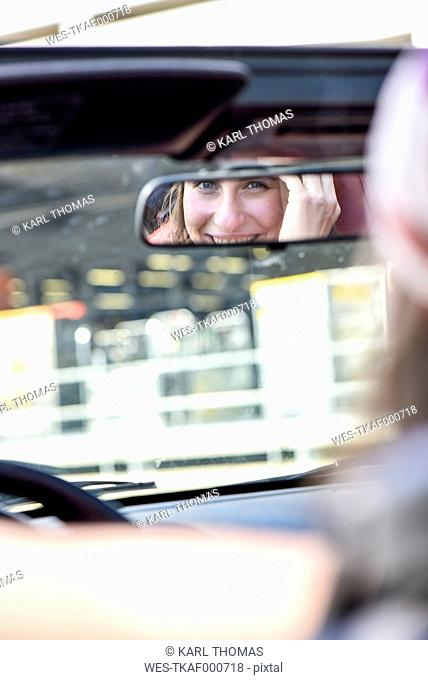 Mirror image of smiling young woman in driving mirror of a convertible