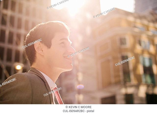 Young city businessman looking up in sunlight