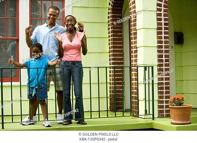 Cheerful family standing by a railing outside a house
