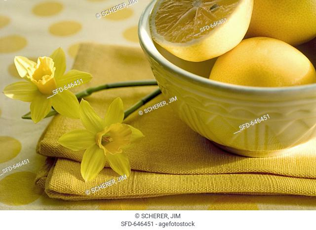 Lemons in bowl and spring snowflake on yellow cloth