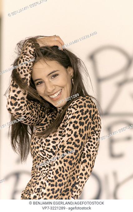 portrait of happy vibrant woman ruffling hair, wearing fashionable leopard print sweater, full of energy, in Munich, Germany