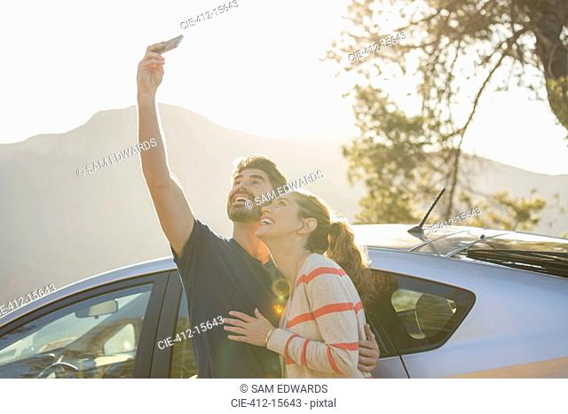 Happy couple taking self-portrait with camera phone outside car