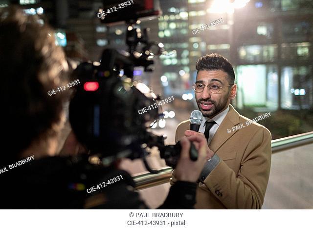 Male journalist and cameraman on urban sidewalk
