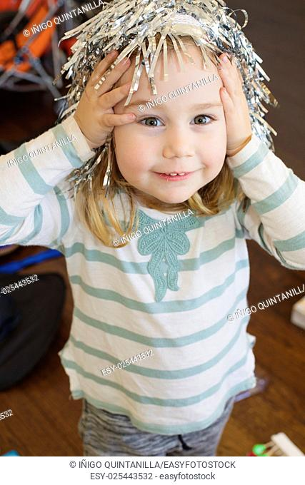 portrait of three years old blonde child with white and green shirt and silver metallic wig on head, looking and smiling, indoor
