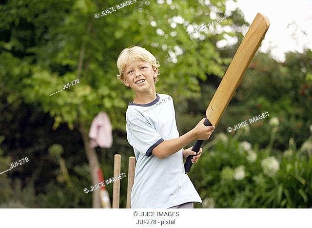 Blonde boy 8-10 playing cricket in garden, swinging bat, smiling