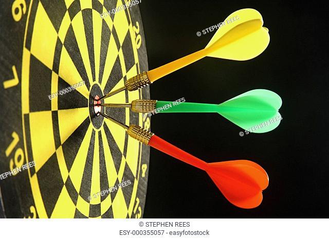Three colourful darts in the bullseye