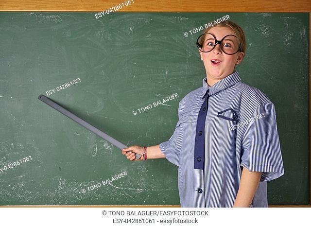 Funny kid girl with teacher costume in green blackboard with school ruller