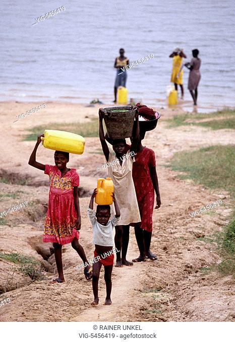 UGA , Uganda : Women and girls are fetching water from the Nile river in Pakwach , August 1991 - Pakwach, Nebbi District, Uganda, 13/08/1991