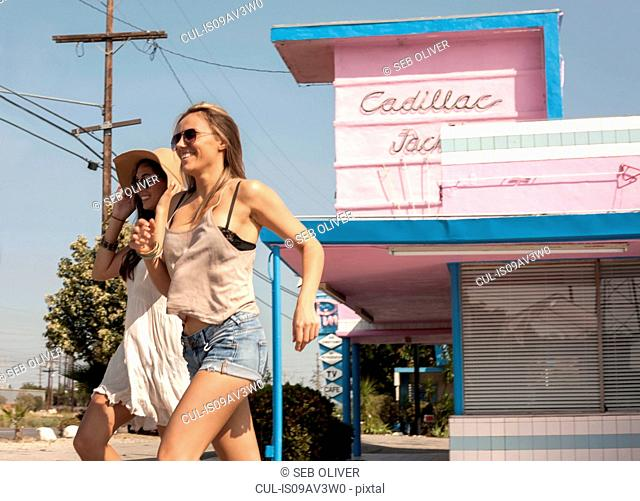 Young women running past motel, Los Angeles, California, USA
