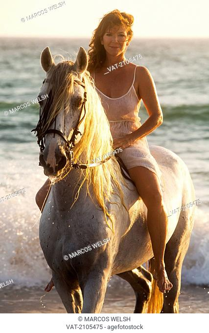 A woman riding a white horse at sunset by the ocean, tarifa cadiz andalusia spain