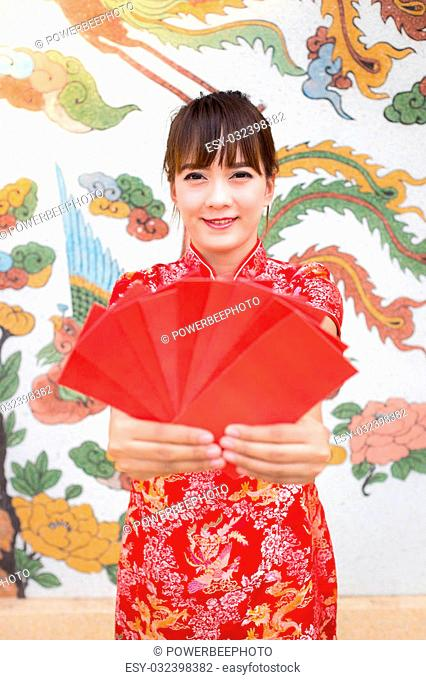 Happy chinese new year,Cute smiling Asian woman dress traditional cheongsam and qipao holding red envelopes ang pow or red packet monetary gift card on chinese...